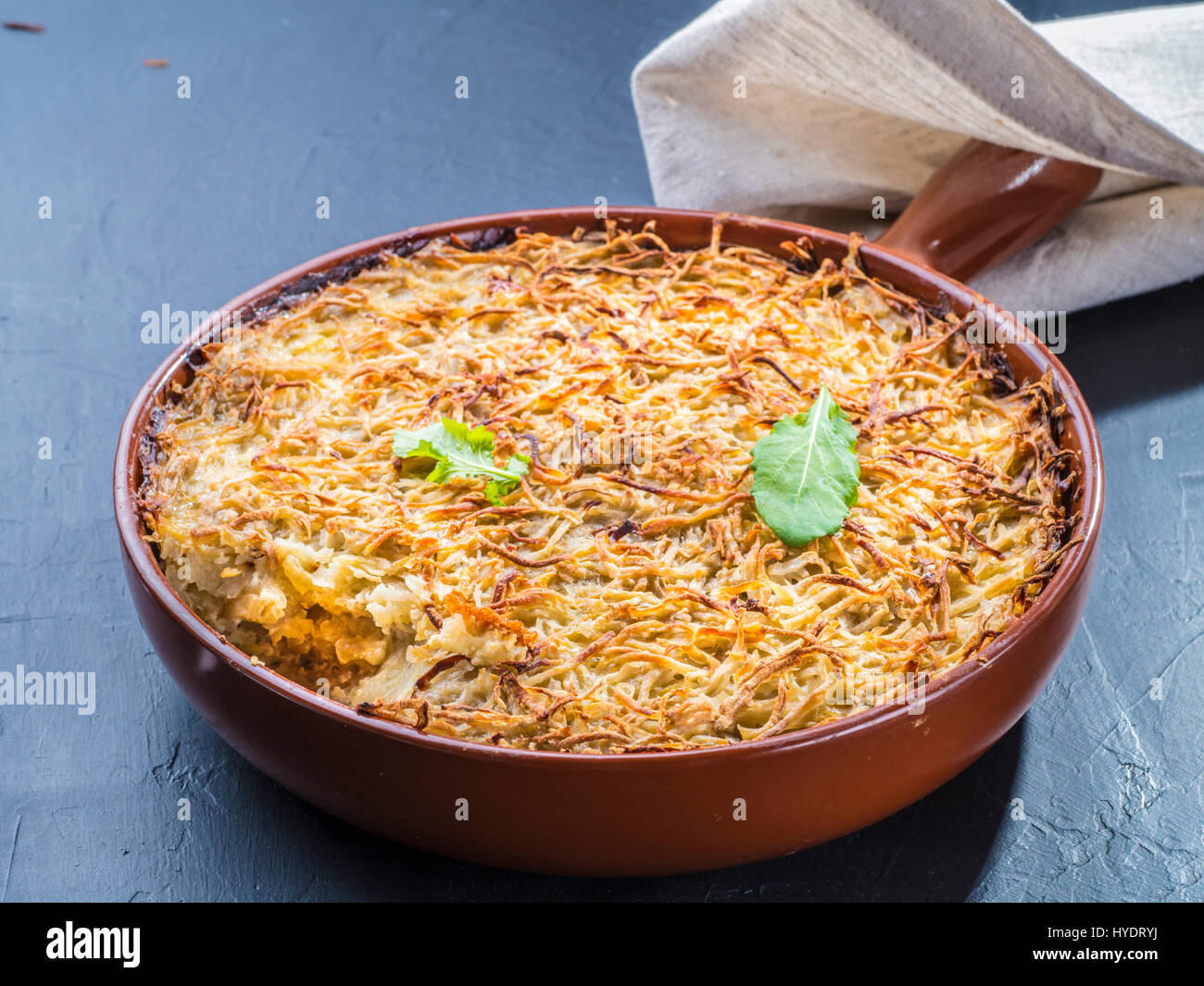 Close up view of appetizing potato casserole with fish, eggs