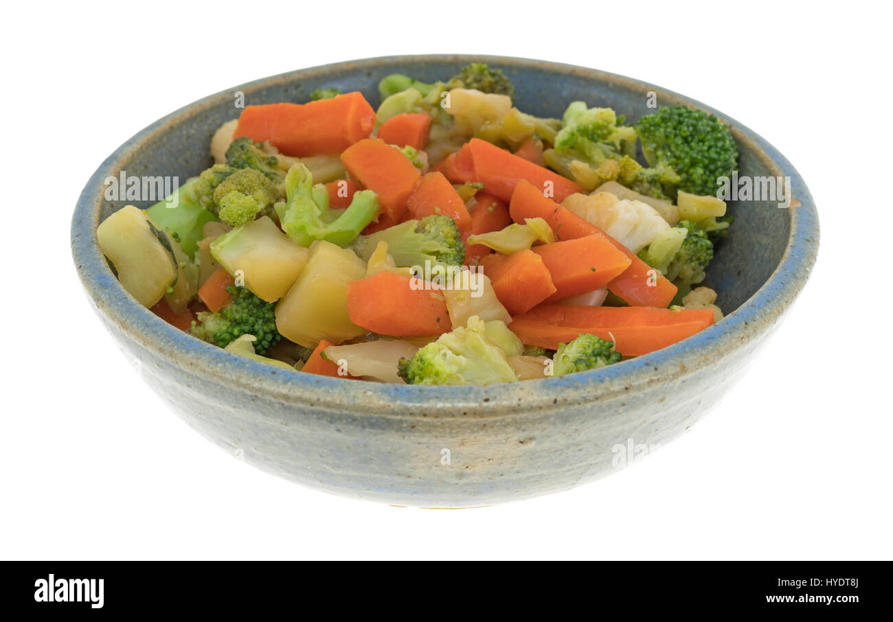 An old stoneware bowl filled with carrots, broccoli and cauliflower in a sauce isolated on a white background. - Stock Image