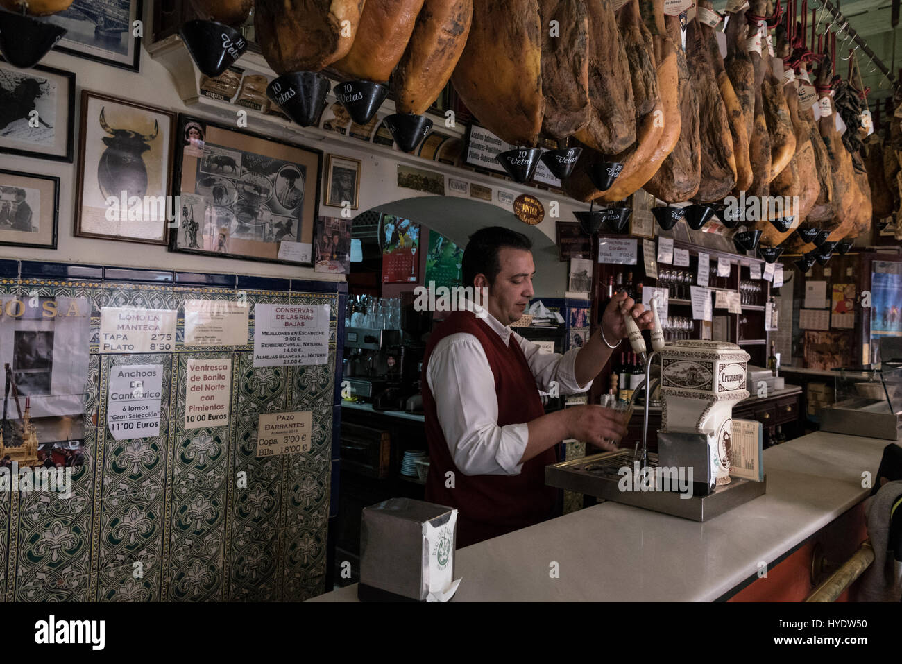 A rack of cured mountain air-dried Jamon Serrano ( Serrano ham shoulder or dry-cured Spanish ham) hang in a row Stock Photo