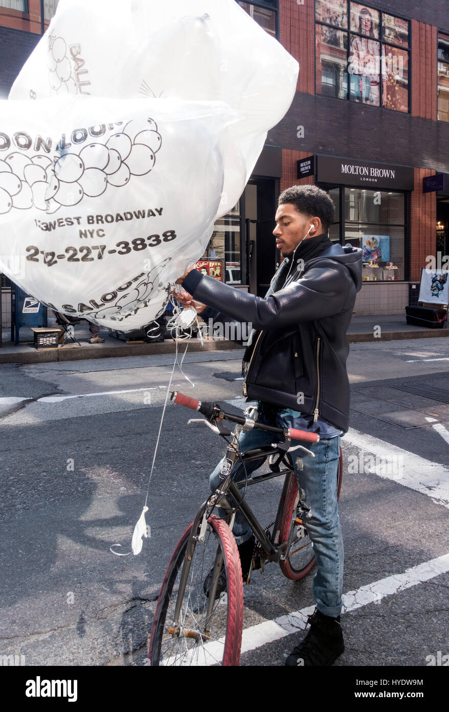 African American man delivering giant PR balloons on a bike - Stock Image