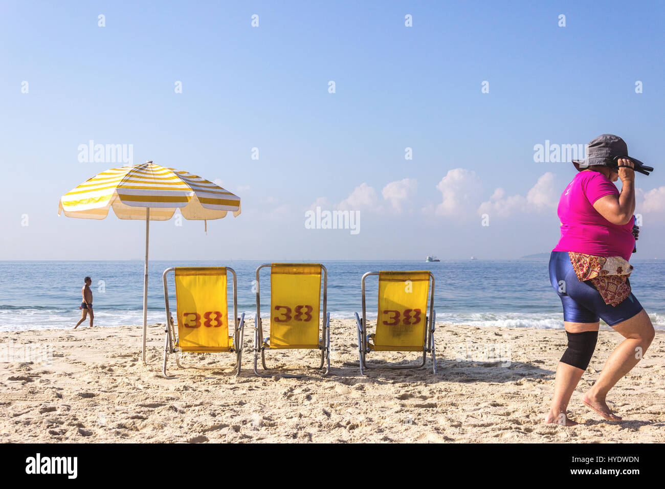 Brazil, Rio de Janeiro: Woman walking on Leme beach and yellow umbrella and chairs - Stock Image