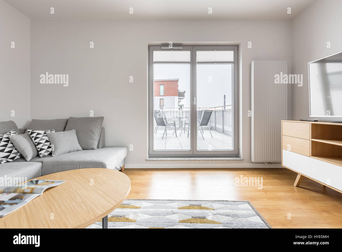 Bright living room with grey sofa, tv, wooden cabinet, table, carpet ...