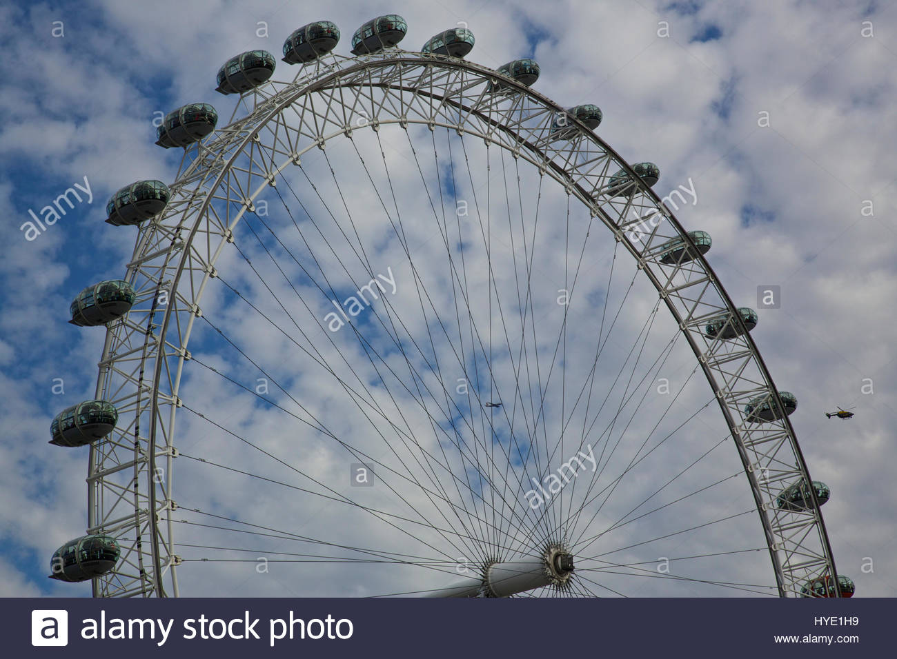The London Eye against a cloudy sky with a helicopter nearby. - Stock Image