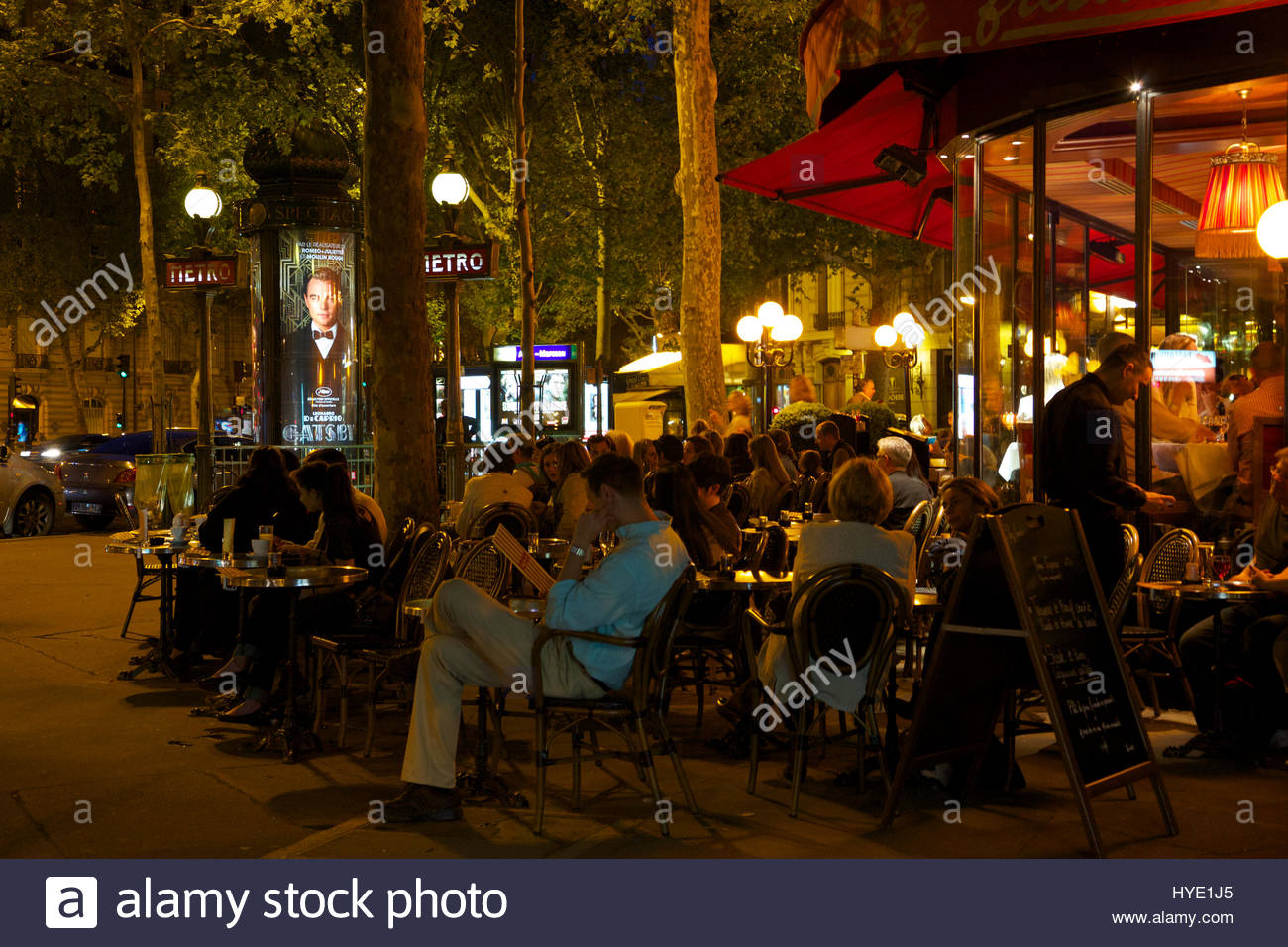 Tourist and locals enjoy spring weather at an outdoor cafe in Paris' 8th Arrondissement. - Stock Image