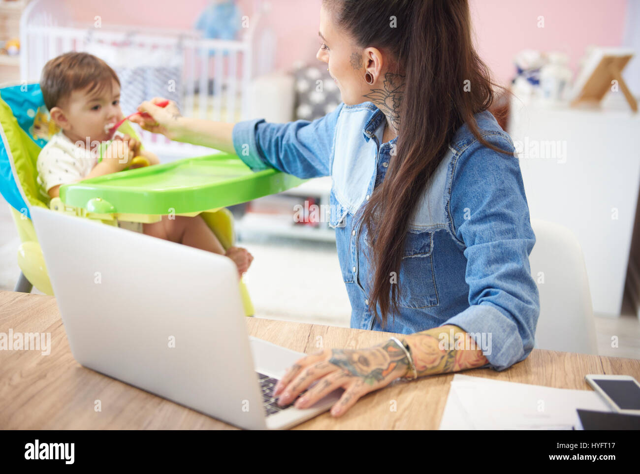Busy mother feeding son and working as well - Stock Image