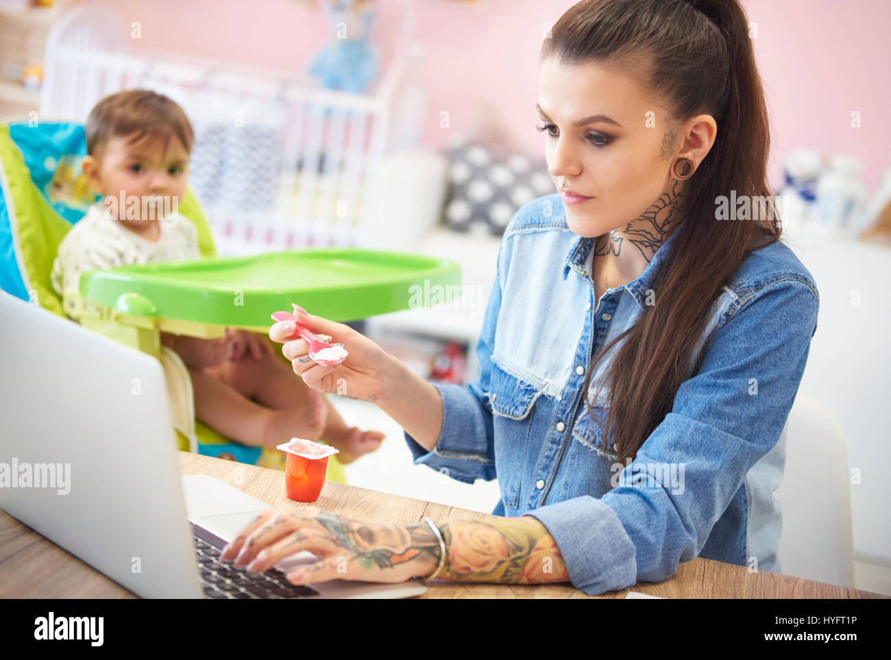 Young mother feeding her baby at home office - Stock Image