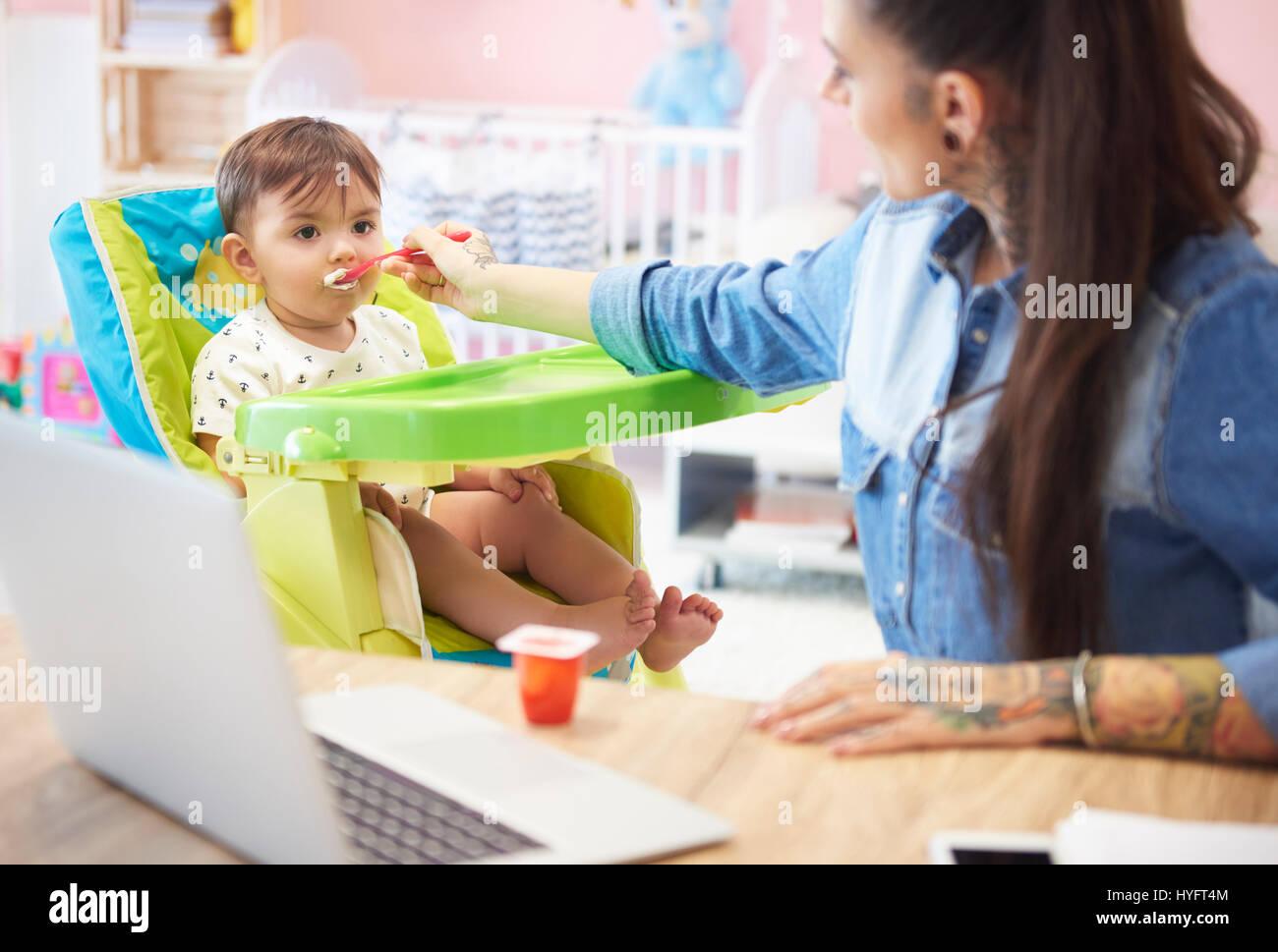 Mother feeding boy with yoghurt - Stock Image
