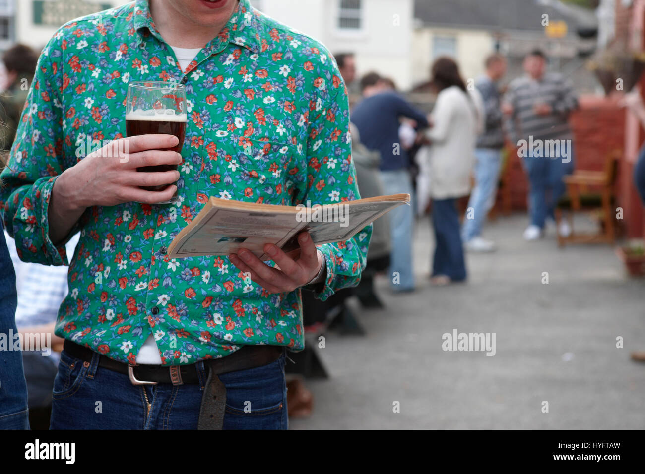 A man wearing a green flowery top reading a book, holding a pint at The Literary Festival, Laugharne, Wales, Uk - Stock Image