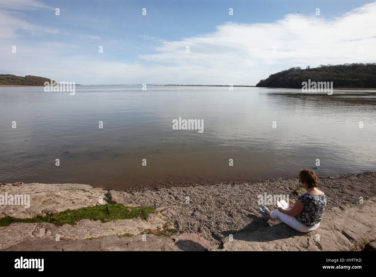 Lady sat by the waters edge reading, The Literary Festival, Laugharne, Wales, Uk - Stock Image