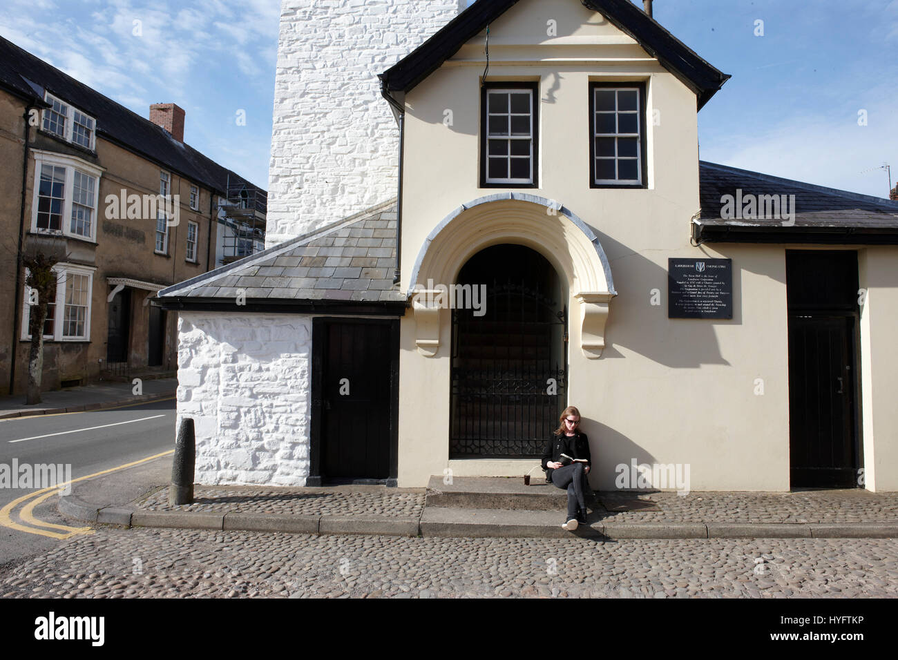 Lady Reading in the sun outside a building, Book Festival, Laugharne - Stock Image
