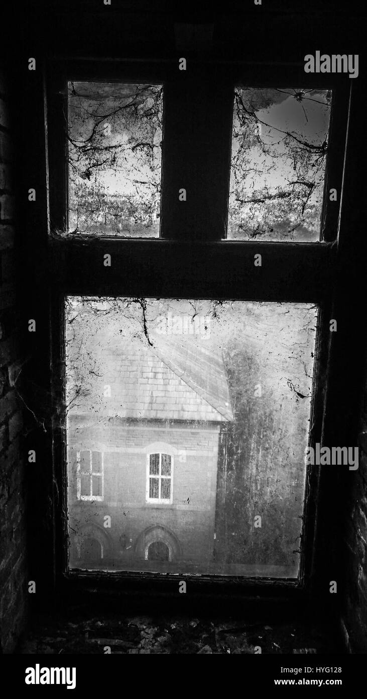 ACCRINGTON LANCASHIRE, ENGLAND: Eerie black and white shot of window covered in cobwebs. WELCOME to the decrepit - Stock Image