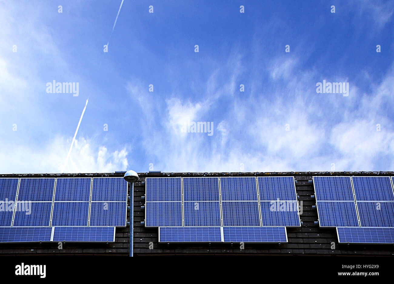 Solar panels on house roof with blue sky in background.Renewable energy source,Stoke on Trent,Staffordshire,United - Stock Image