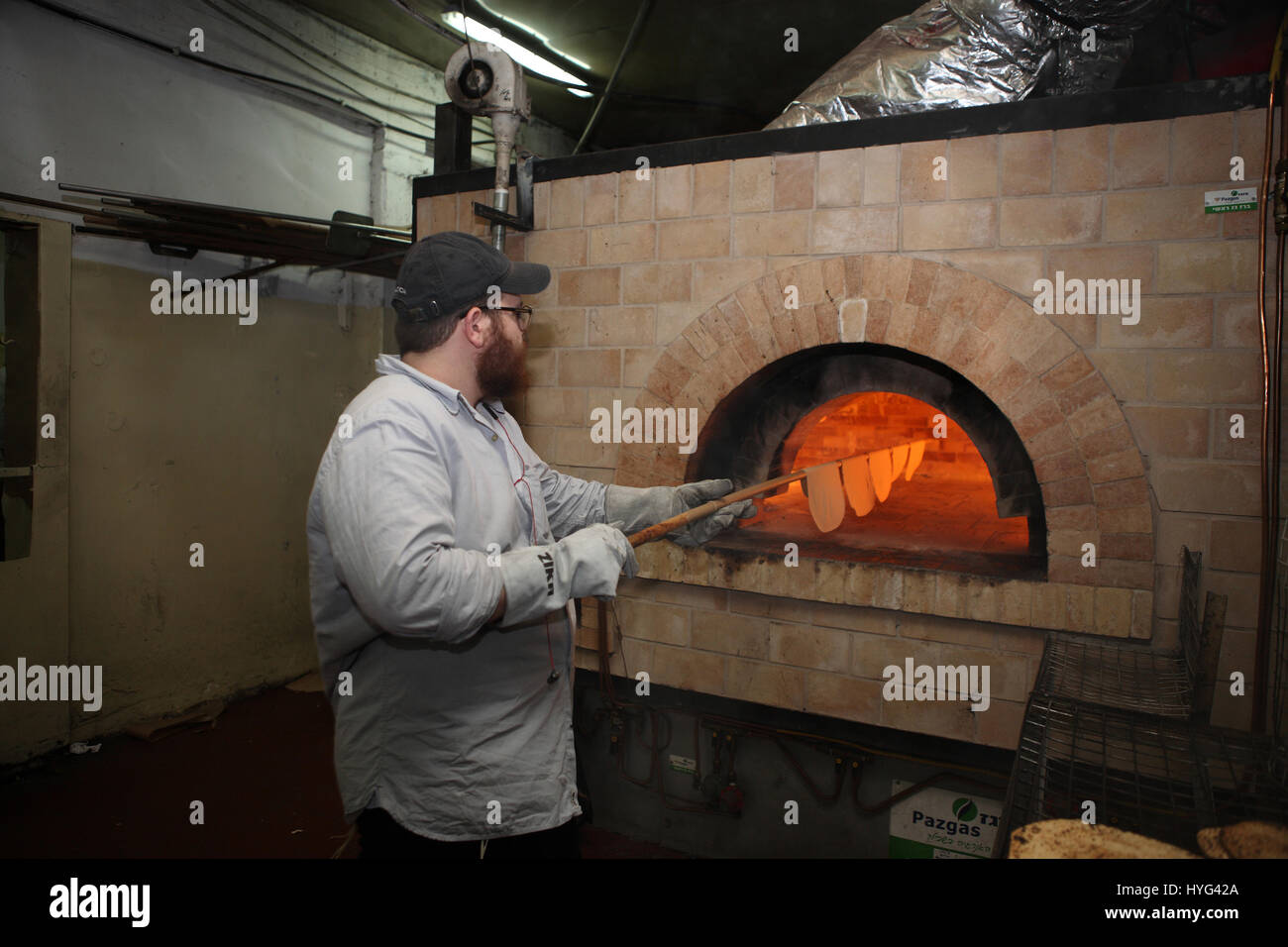 A Hasidic man uses a long stick to put flattened pieces of dough in the oven to bake Matza or Matzah Shmura for - Stock Image