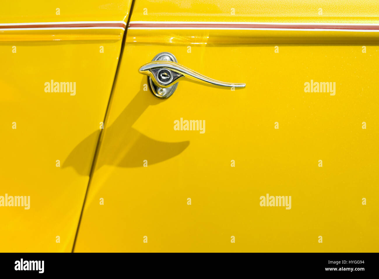 lever and glittering door panel of a bright yellow vehicle - Stock Image
