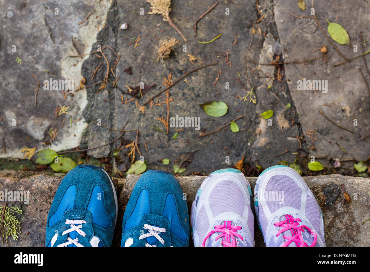 top view of a two pairs of sneakers shoes on paving stone Stock Photo