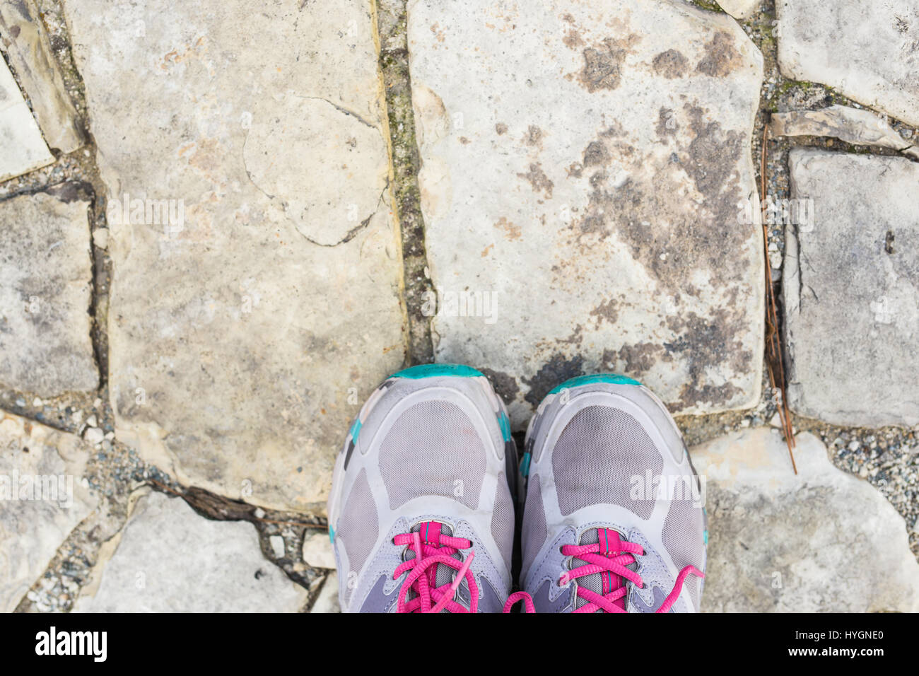 top view of pair of sneakers shoes on paving stone Stock Photo
