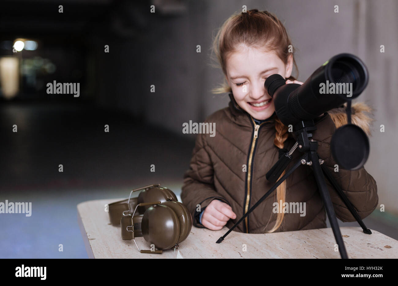 Positive cheerful girl looking into the telescope - Stock Image