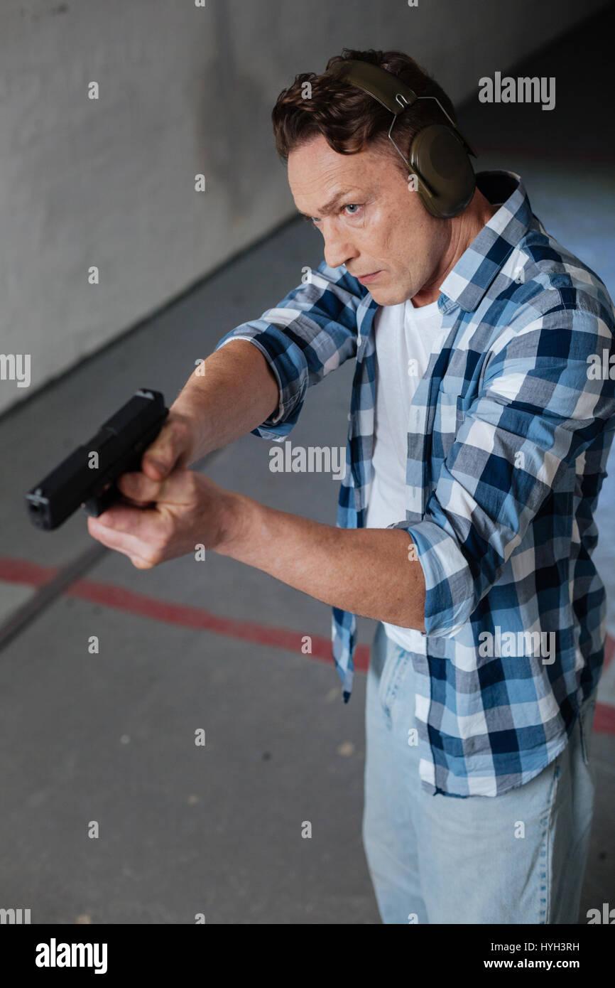 Handsome good looking man directing his handgun - Stock Image