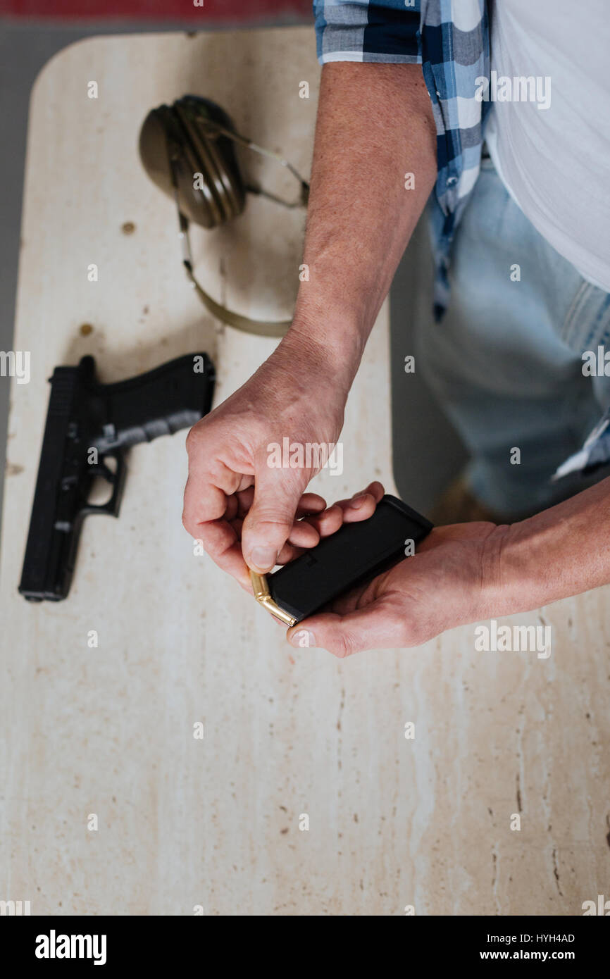 Handsome brutal man holding the cartridge clip - Stock Image
