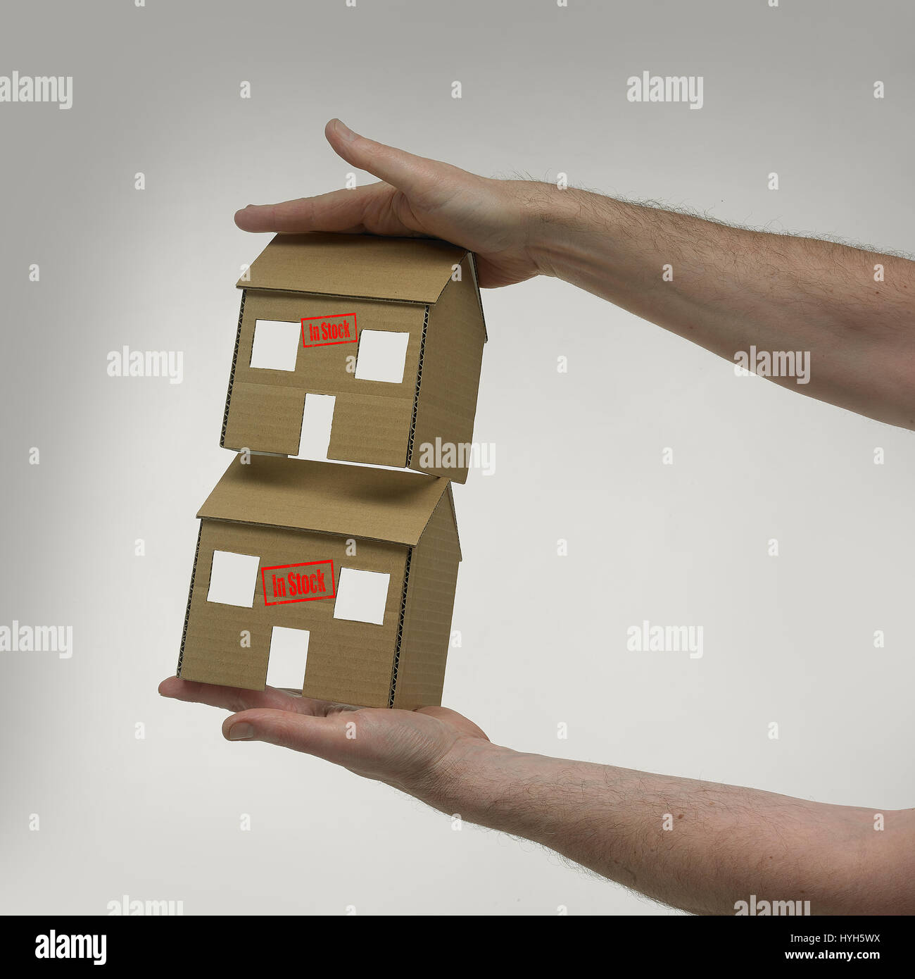 Two Cardboard Houses with an 'in stock' stamp. Stock Photo