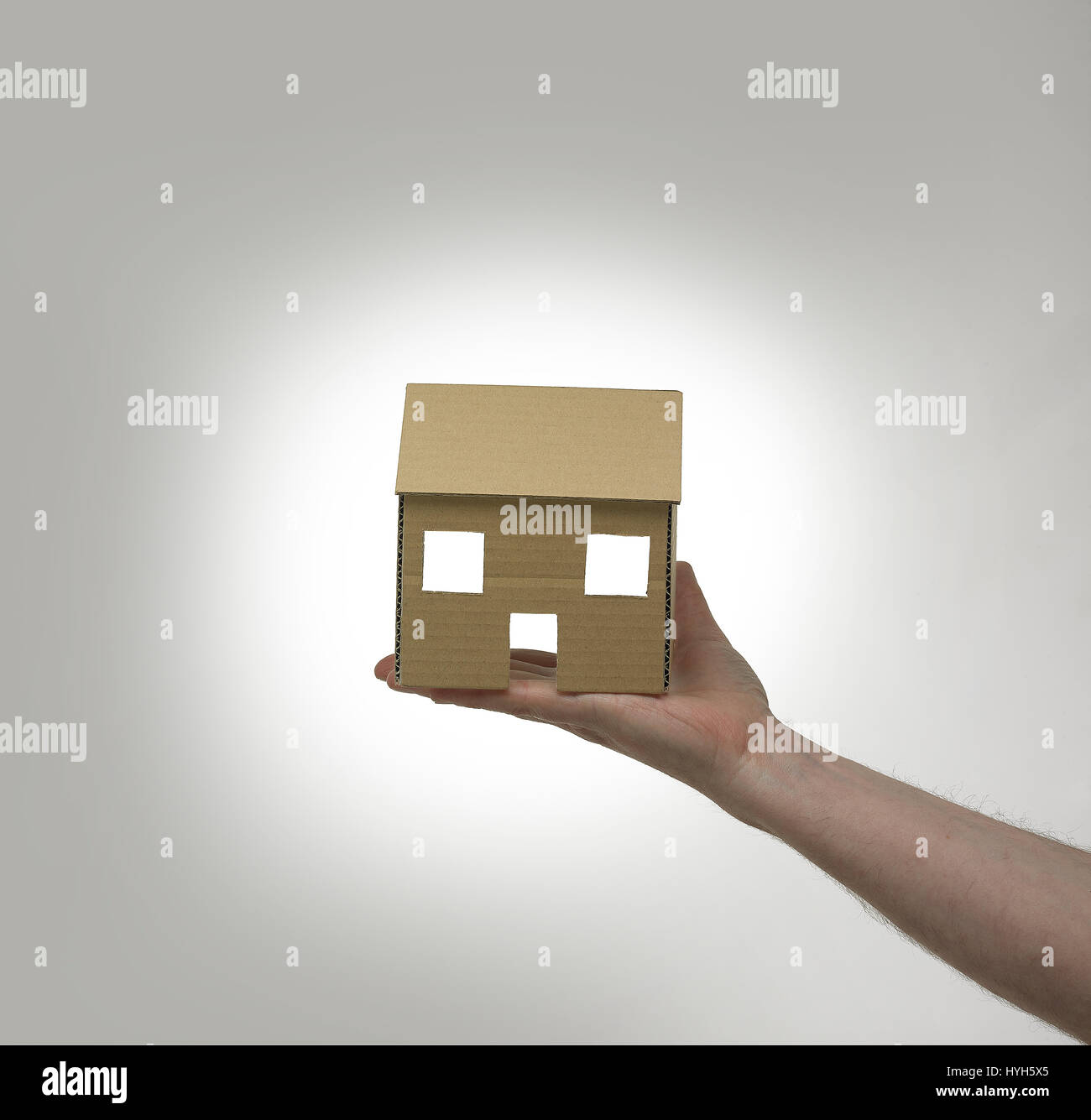 Cardboard House held in hand. Stock Photo