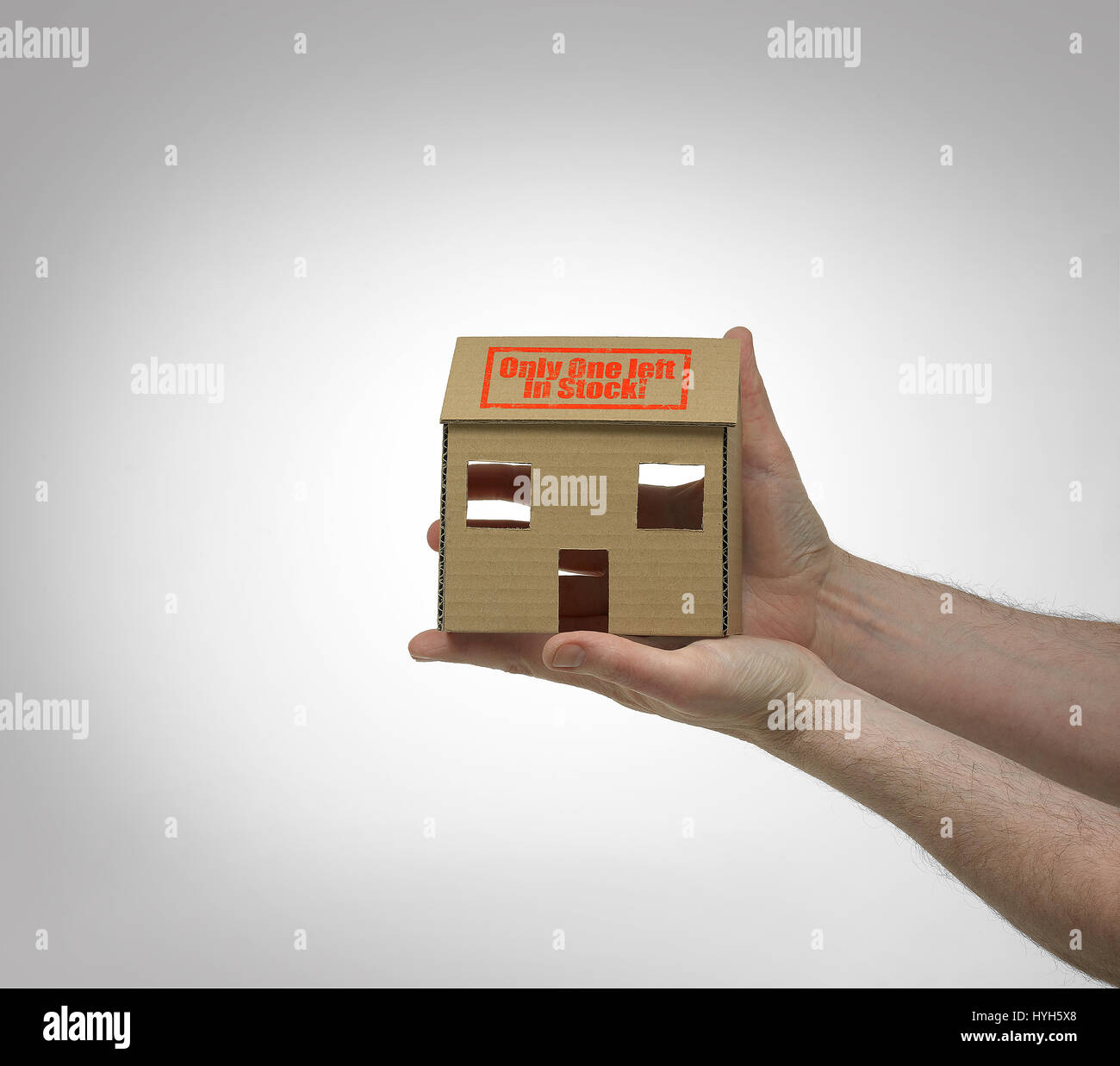 Cardboard House held in hands and only one left in stock! Stock Photo