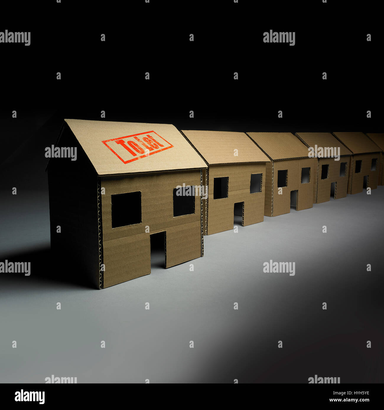 Row of Cardboard Houses with one to let. Stock Photo