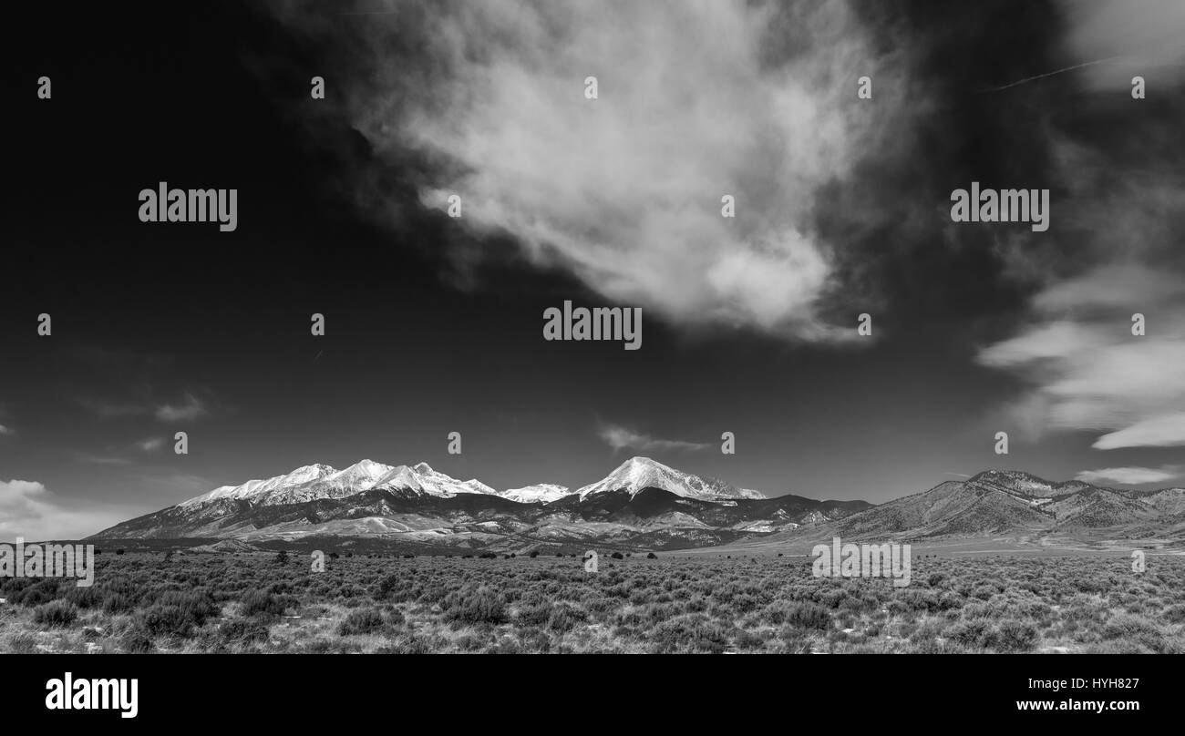 Black and white panorama of snow capped mountains in open field - Stock Image