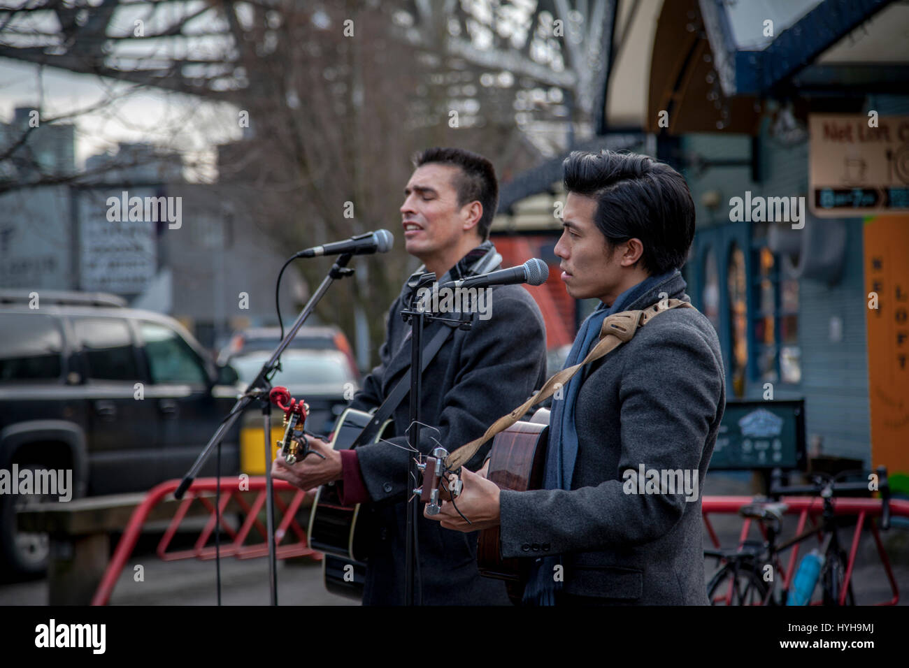 Young guitarists and singer performing outdoors, Granville Island, Vancouver, British Columbia, Canada - Stock Image