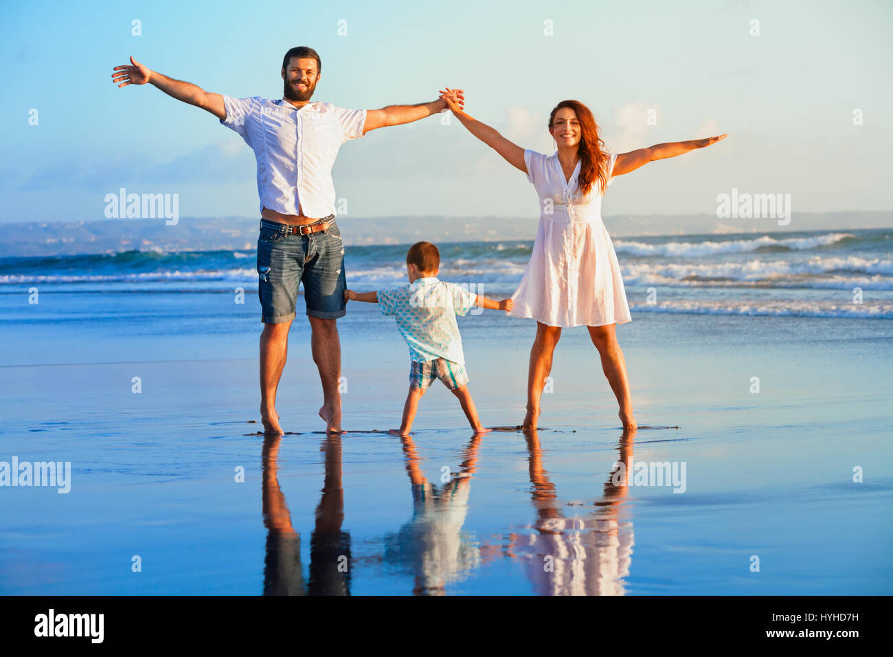 Happy family - father, mother, baby son hold hands, walk and jump together by water pool on sunset black sand beach - Stock Image