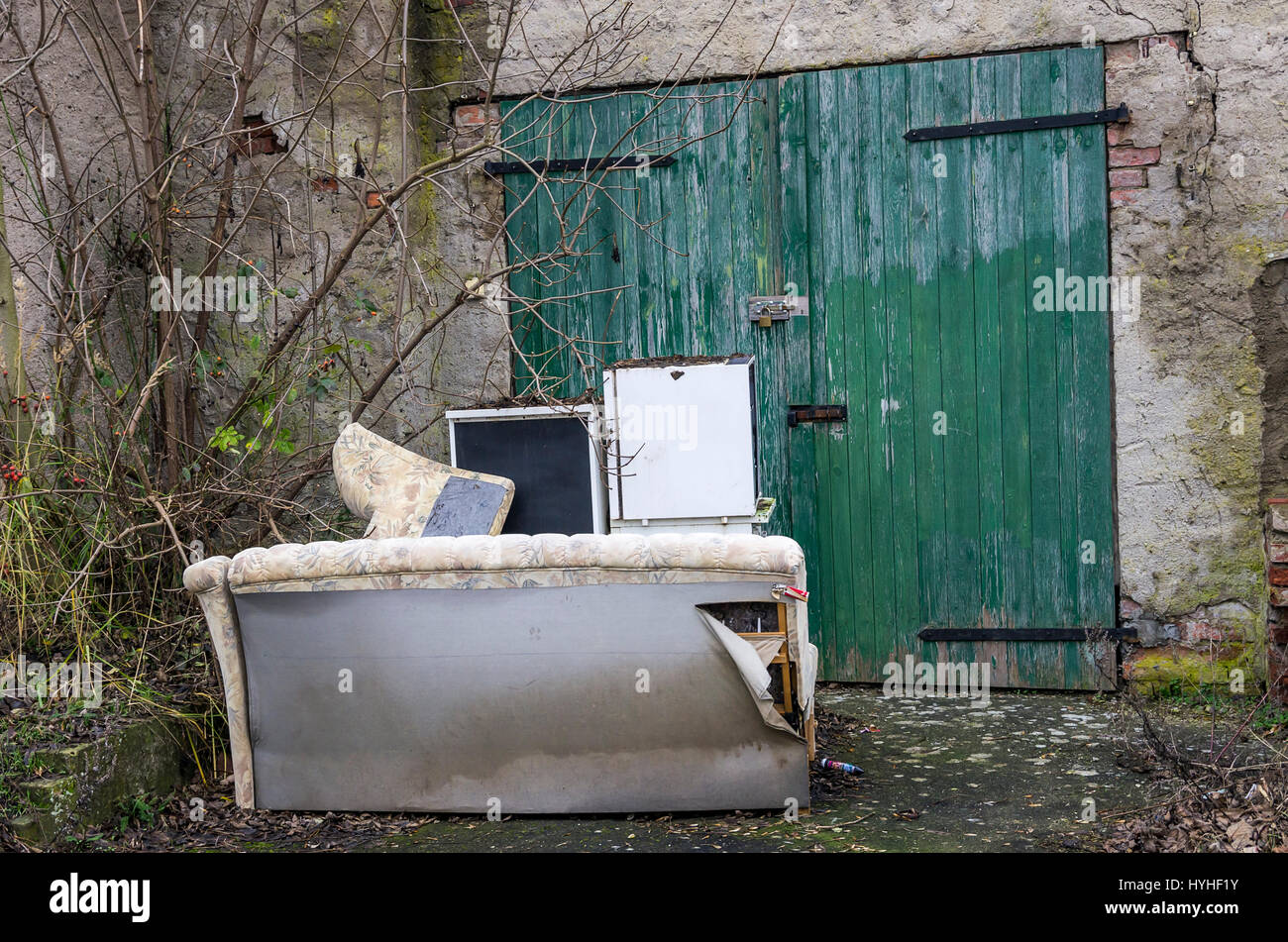 Old garage door with bulky waste idyll. - Stock Image