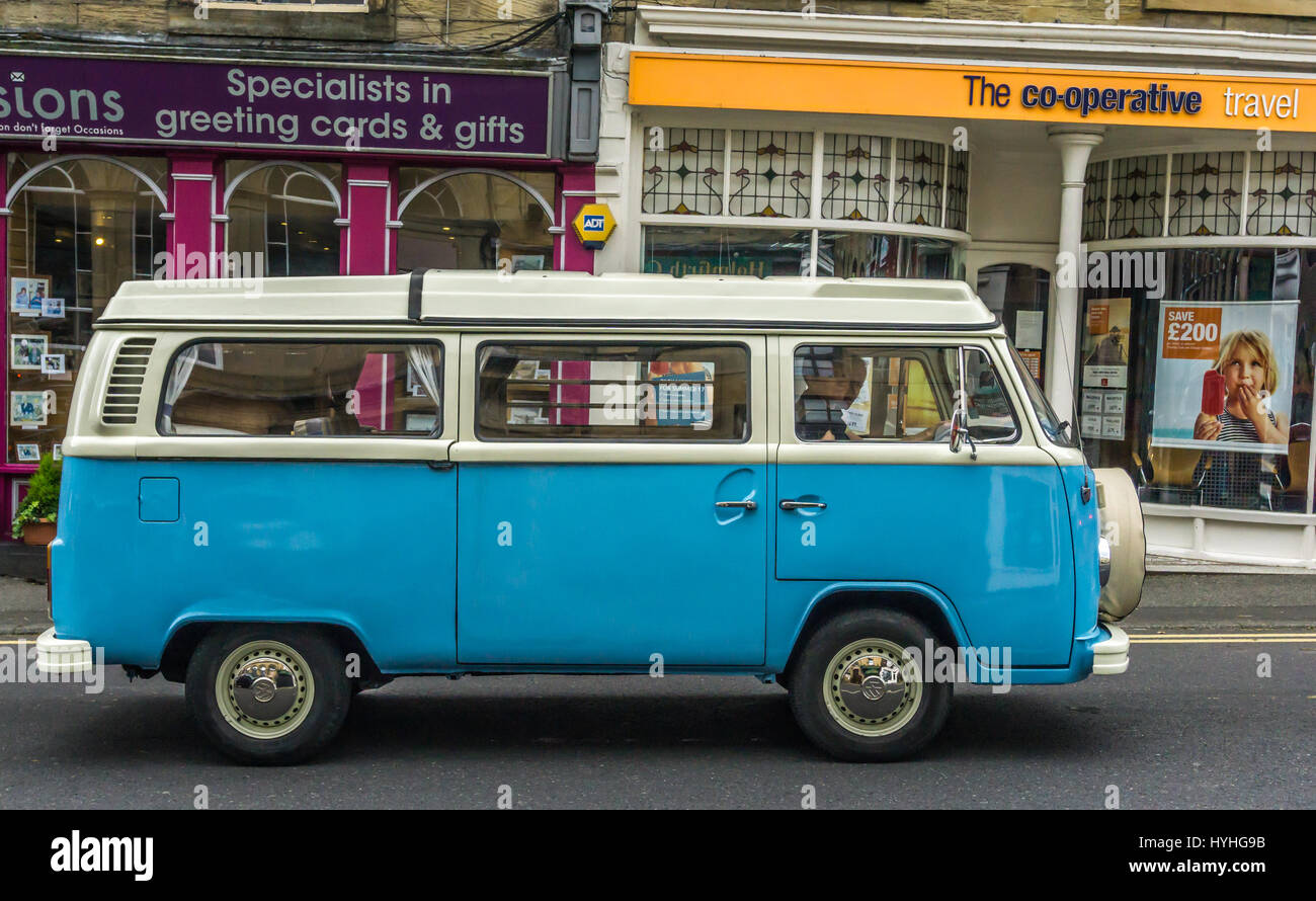 Blue VW camper van driving through Holmfirth village. - Stock Image