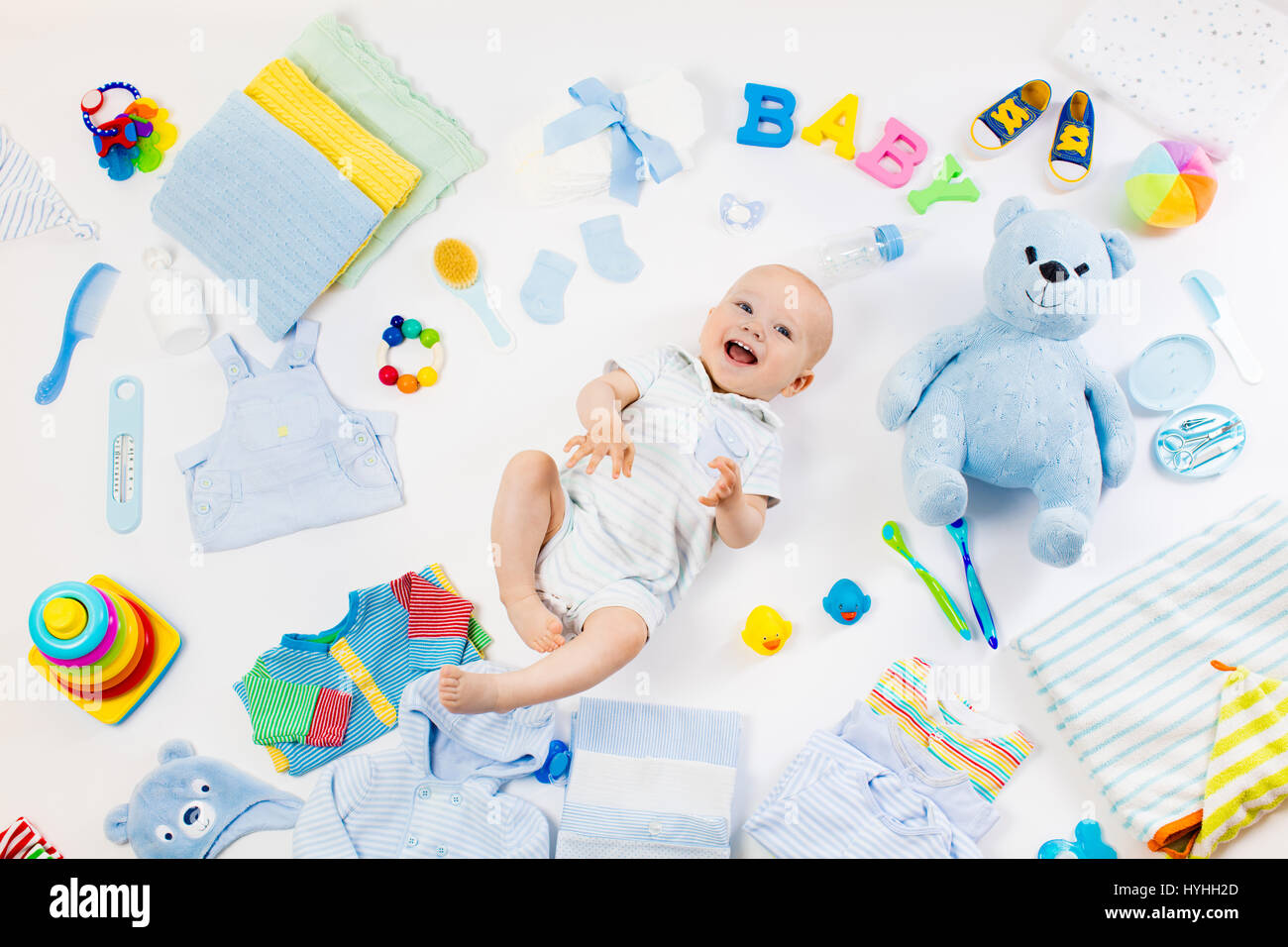 Baby On White Background With Clothing Toiletries Toys And Health