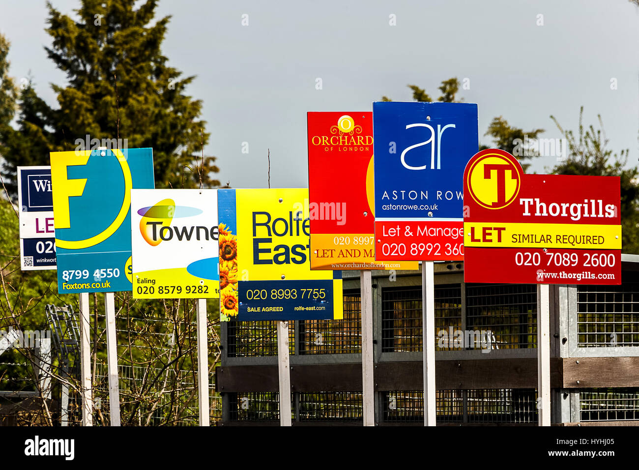 Multiple advertised boards from different estate agents outside a property Stock Photo