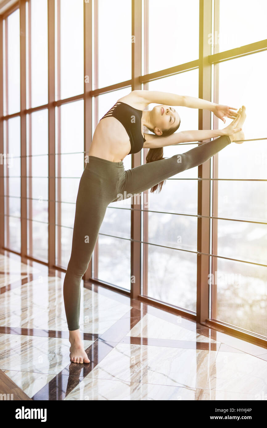 Full length side view portrait of beautiful young woman working out in luxury fitness center, doing yoga hasta padangusthasana - Stock Image