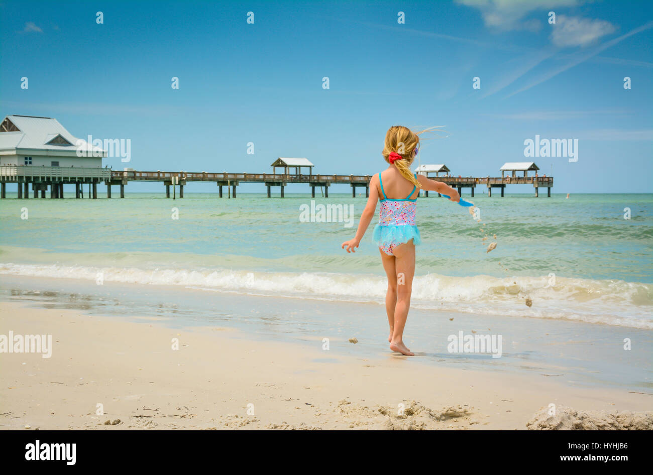Rear view of young blond girl in blue bathingsuit plays on white sand beach at Clearwater Beach, FL with Pier 60 - Stock Image