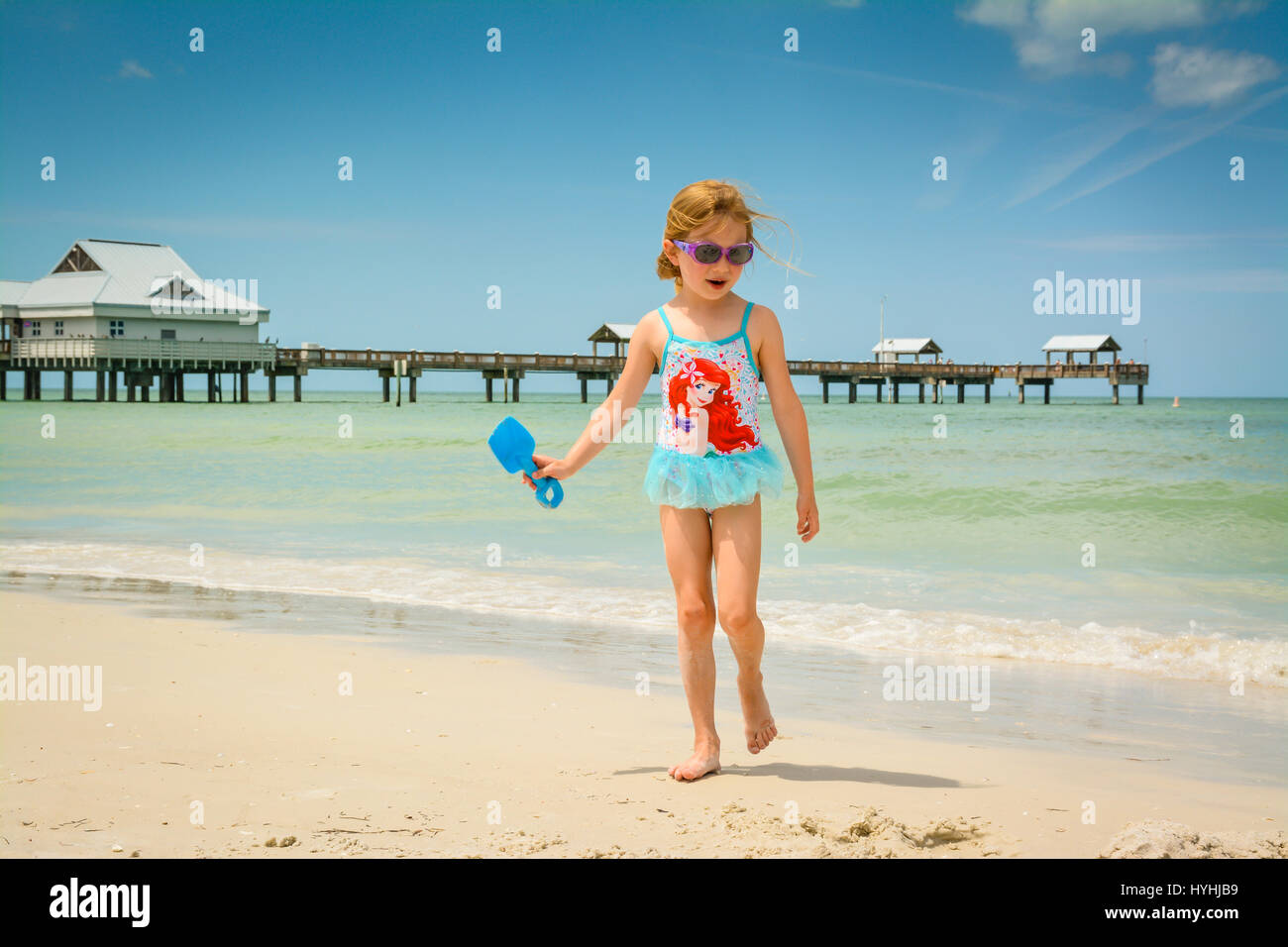 young blond girl in blue bathingsuit plays on white sand beach at Clearwater Beach, FL with Pier 60 and the shoreline - Stock Image