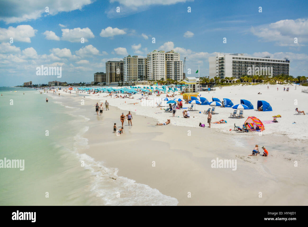 Long overview of people strolling, wading, swimming, sunbathing  & enjoying the white sand and turquoise waters - Stock Image