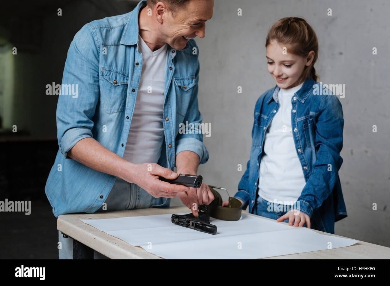 Delighted cheerful father pointing at the disassembled gun - Stock Image