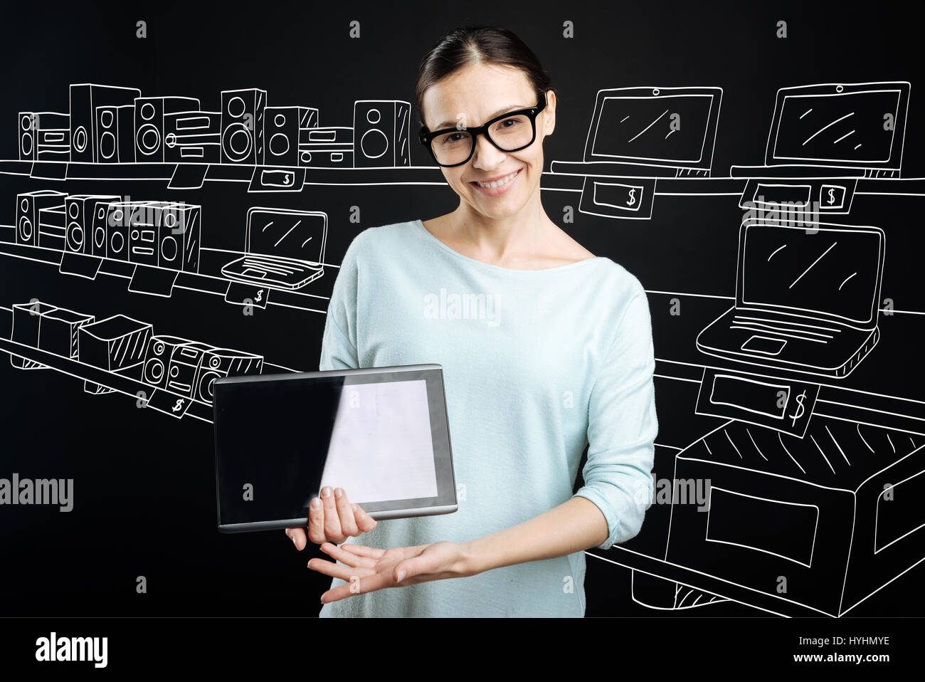Positive shop assistant selling electronics - Stock Image