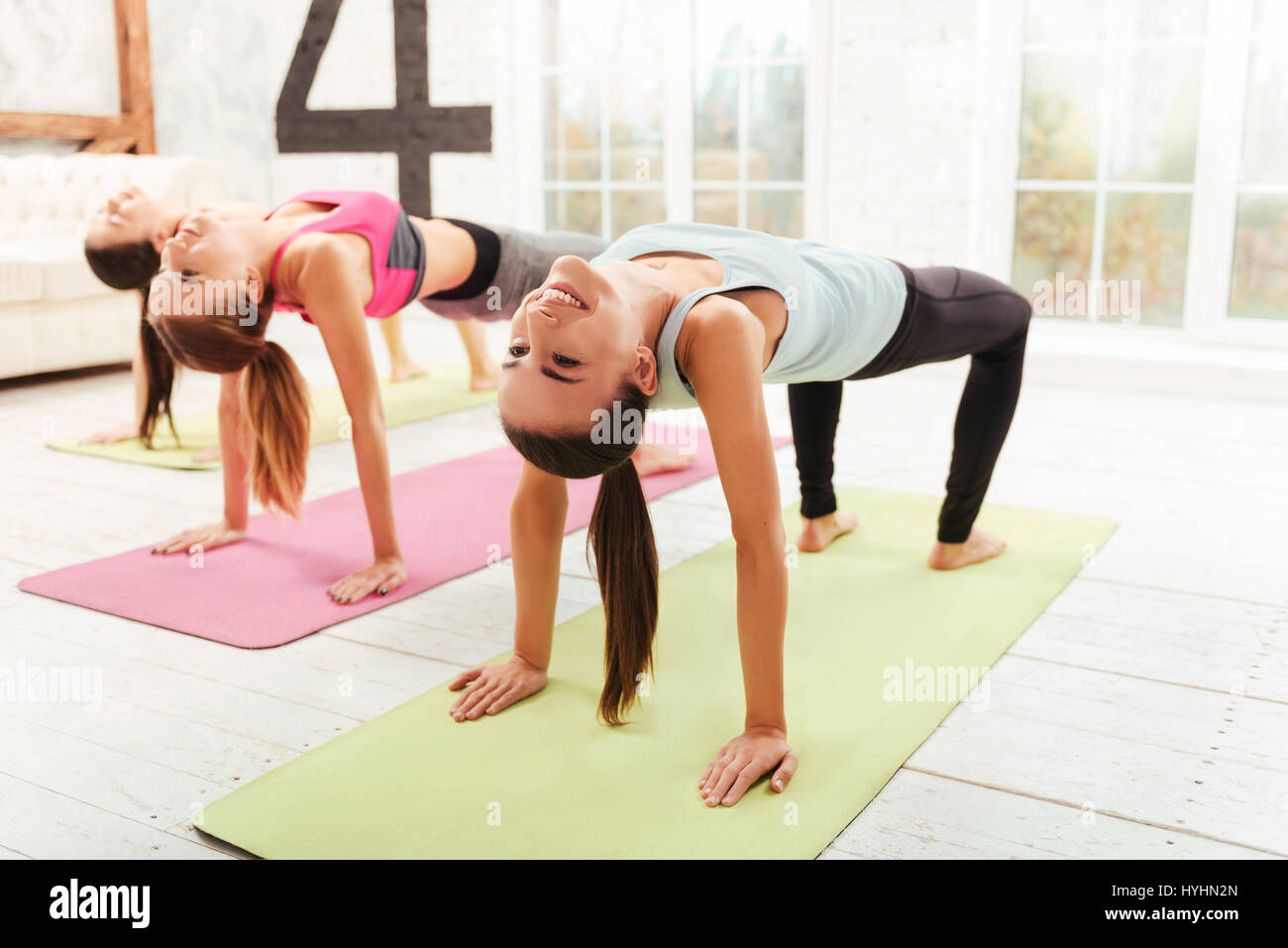Smiling women doing gymnastic exercises. - Stock Image