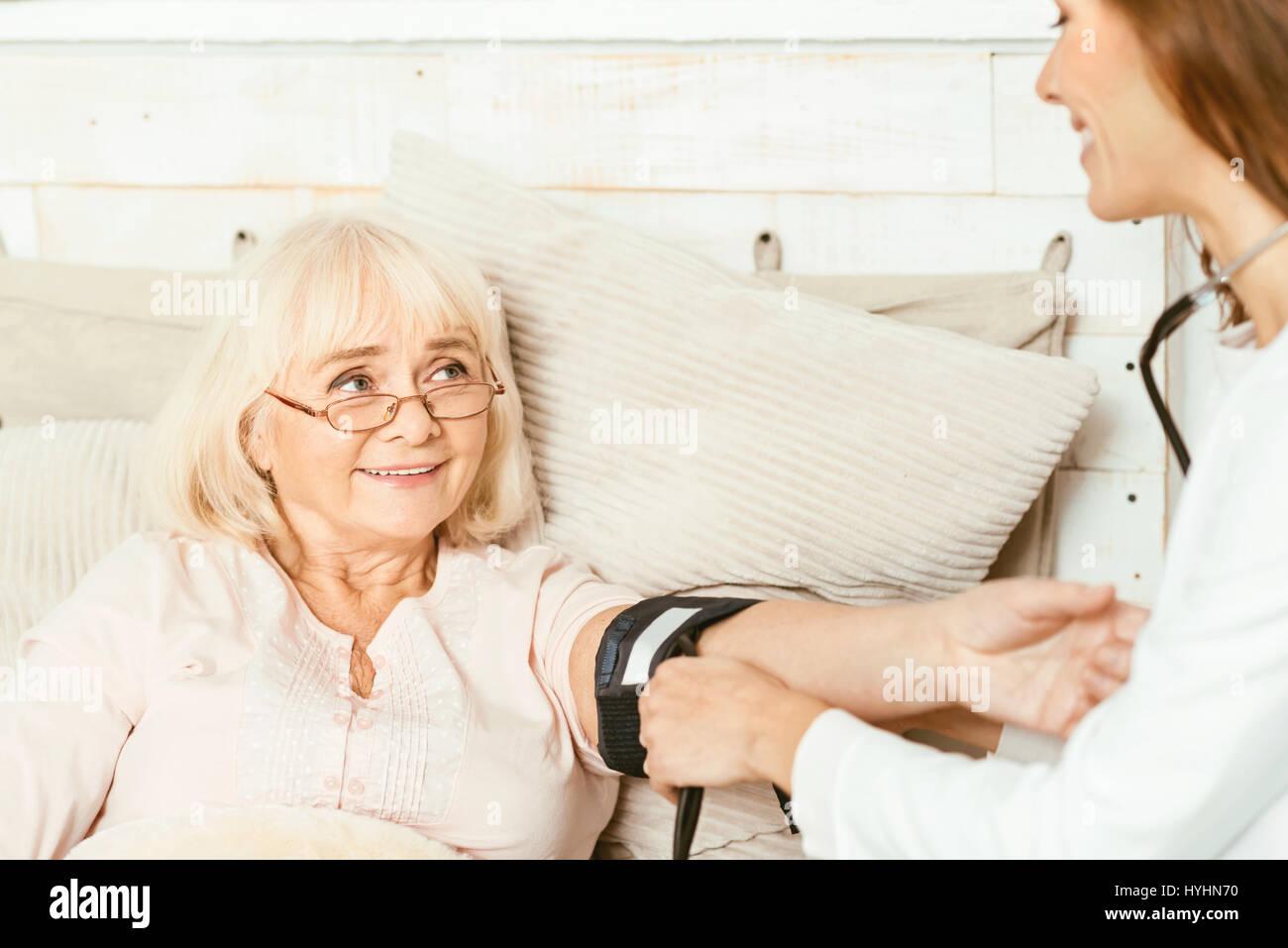 Skillful caregiver measuring pensioners blood pressure at home - Stock Image