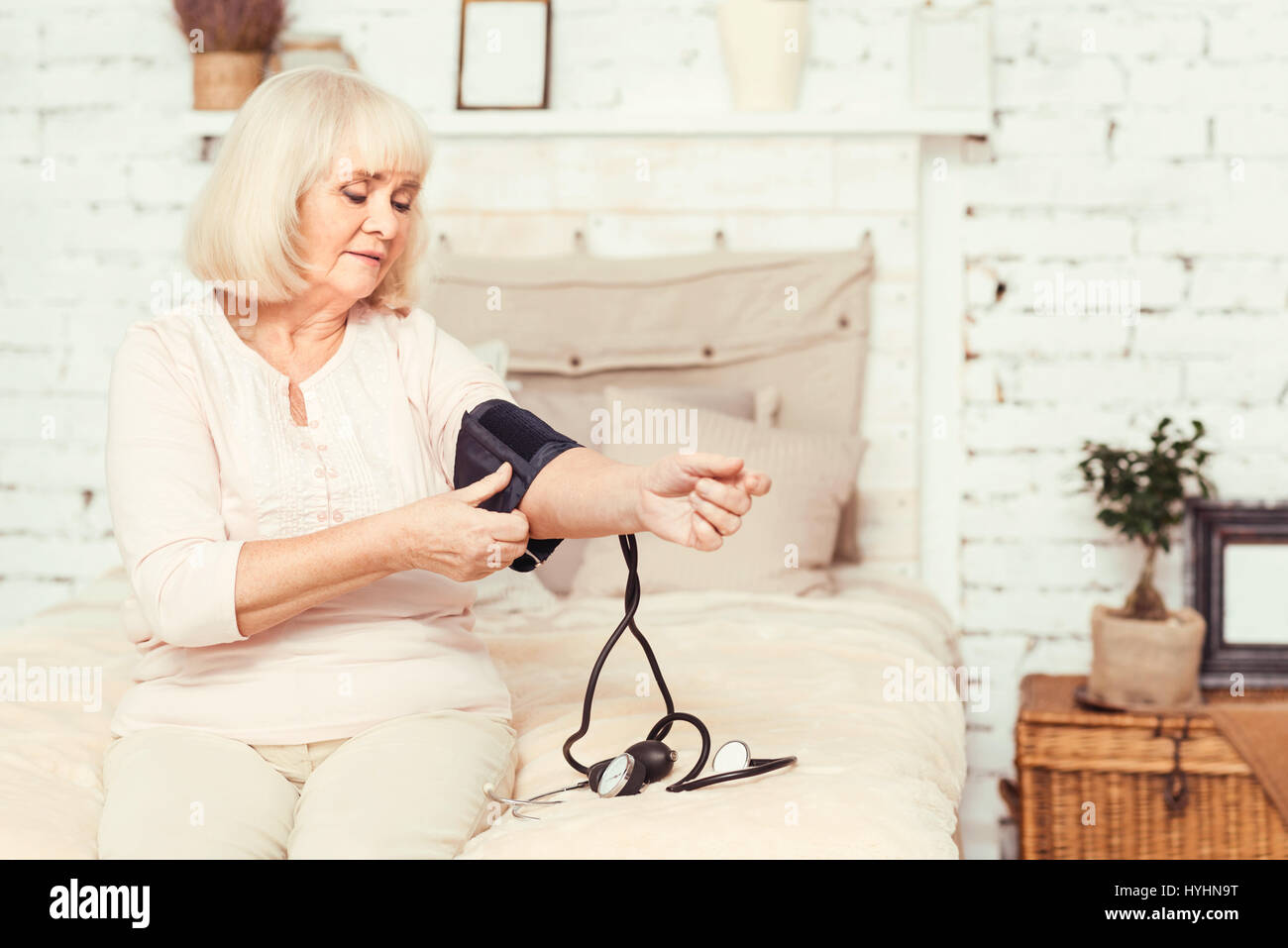 Skillful elderly lady measuring blood pressure at home - Stock Image