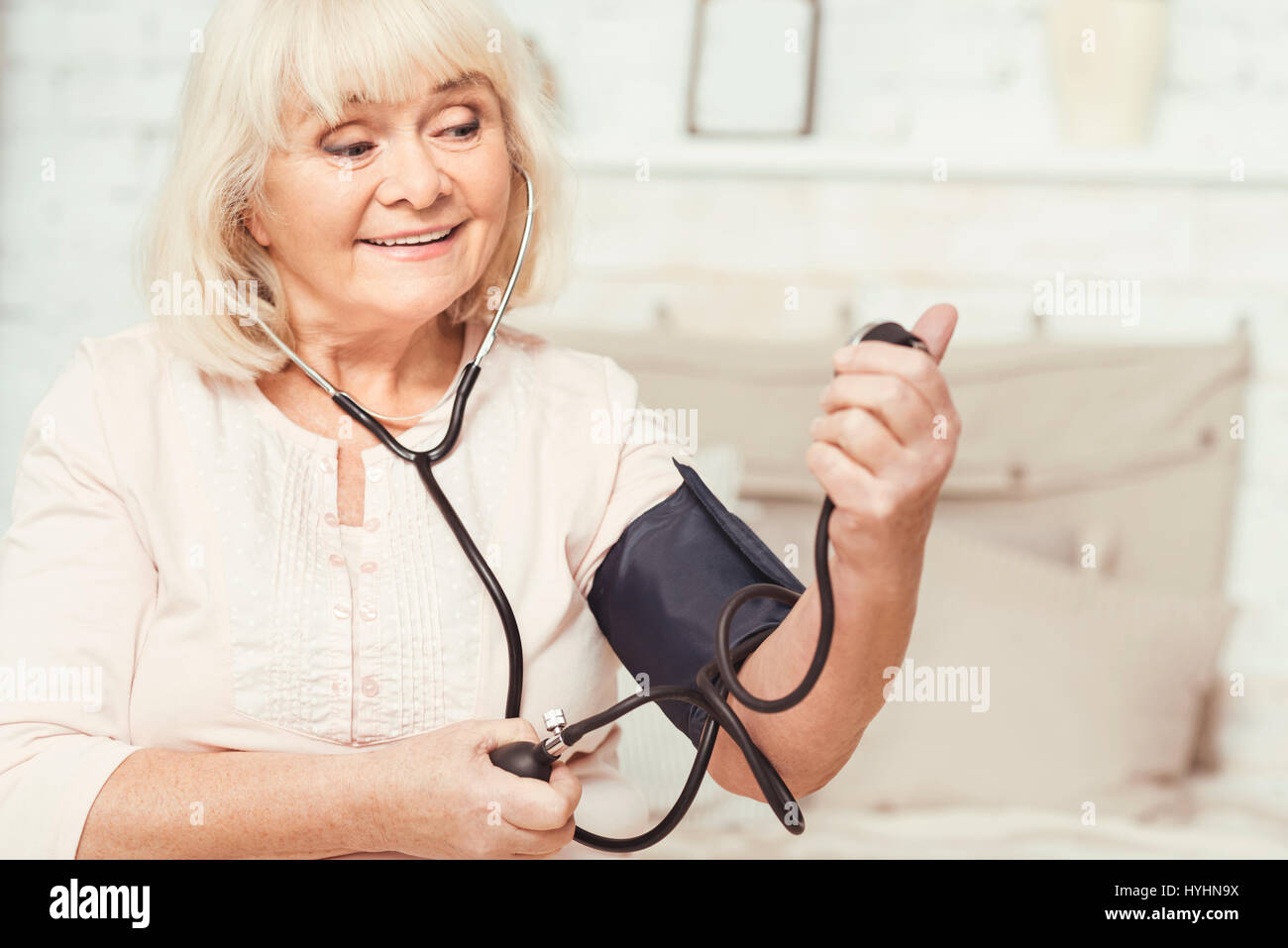 Cheerful aged woman checking blood pressure at home - Stock Image