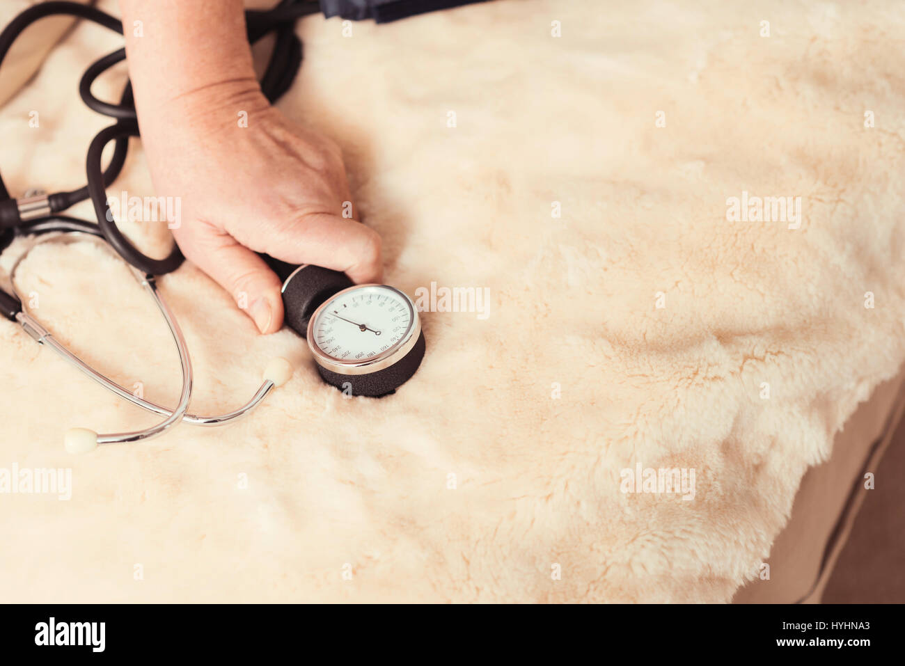 Aged woman holding tonometer at home - Stock Image