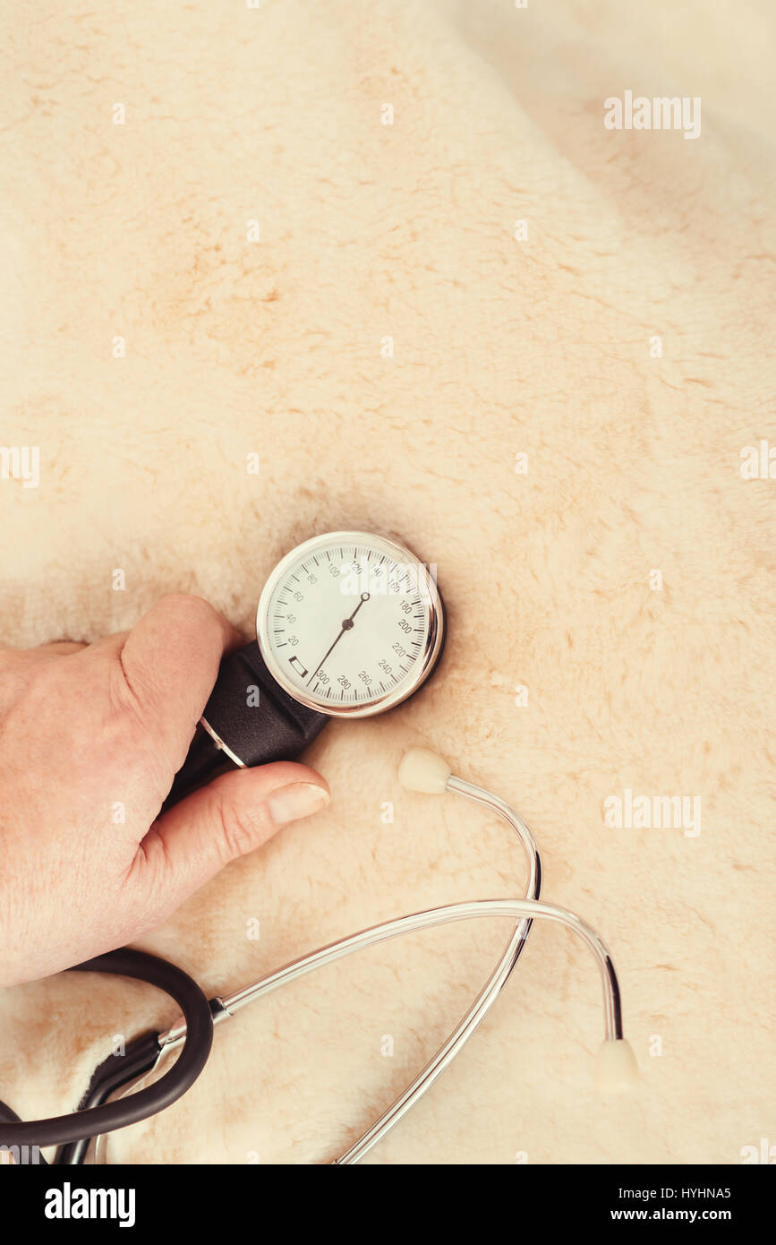 Old female hand touching tonometer - Stock Image