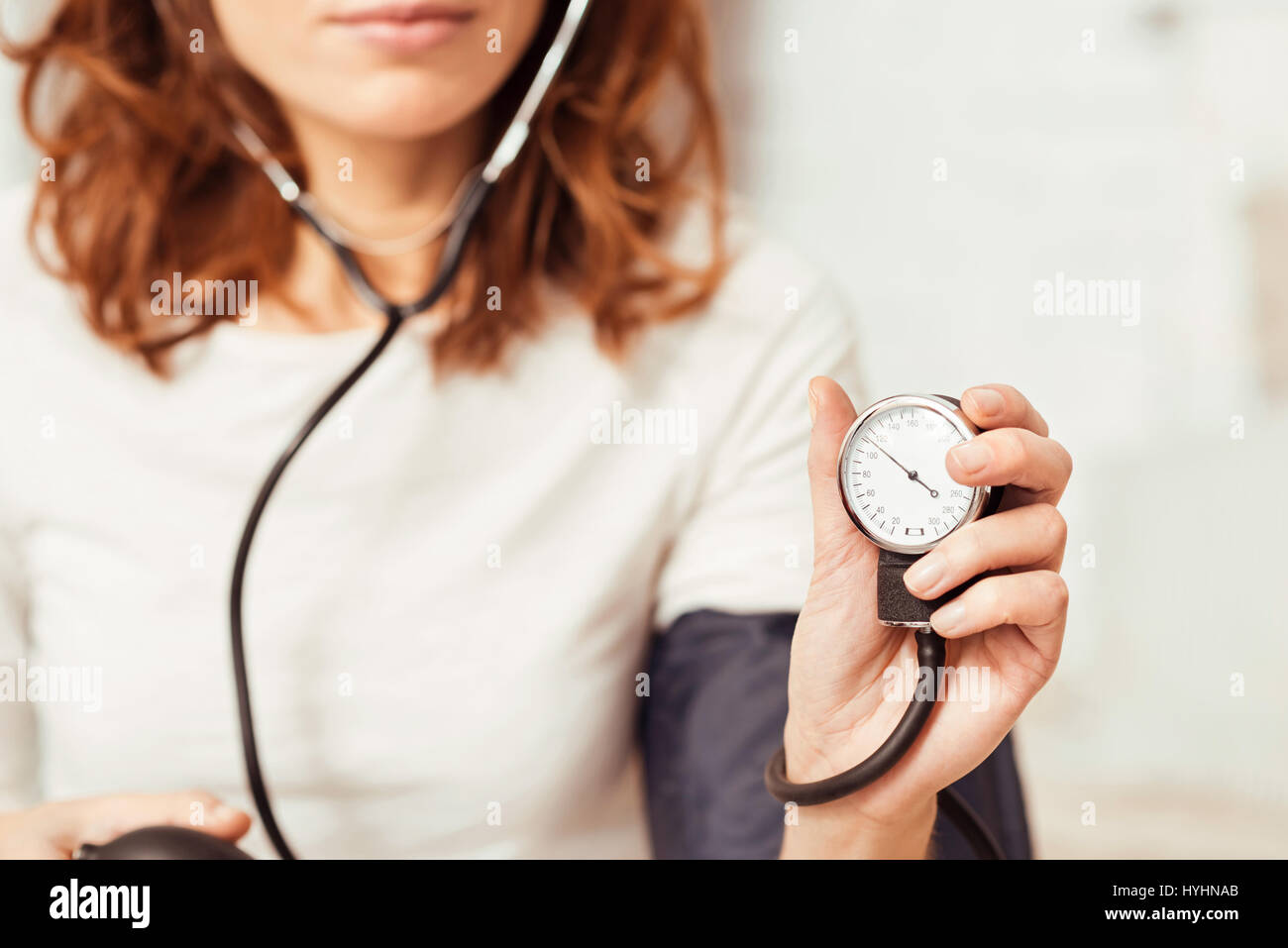 Concentrated young woman demonstrating blood pressure index at home - Stock Image