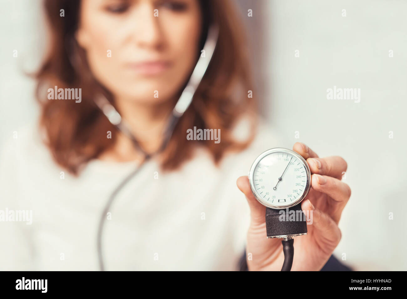 Serious young woman demonstrating blood pressure index at home - Stock Image
