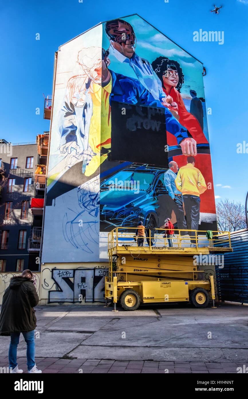 Berlin, Mitte. Mural  Mercedes-Benz advertisement. Painting by commercial artists - Man operating drone for photograph - Stock Image