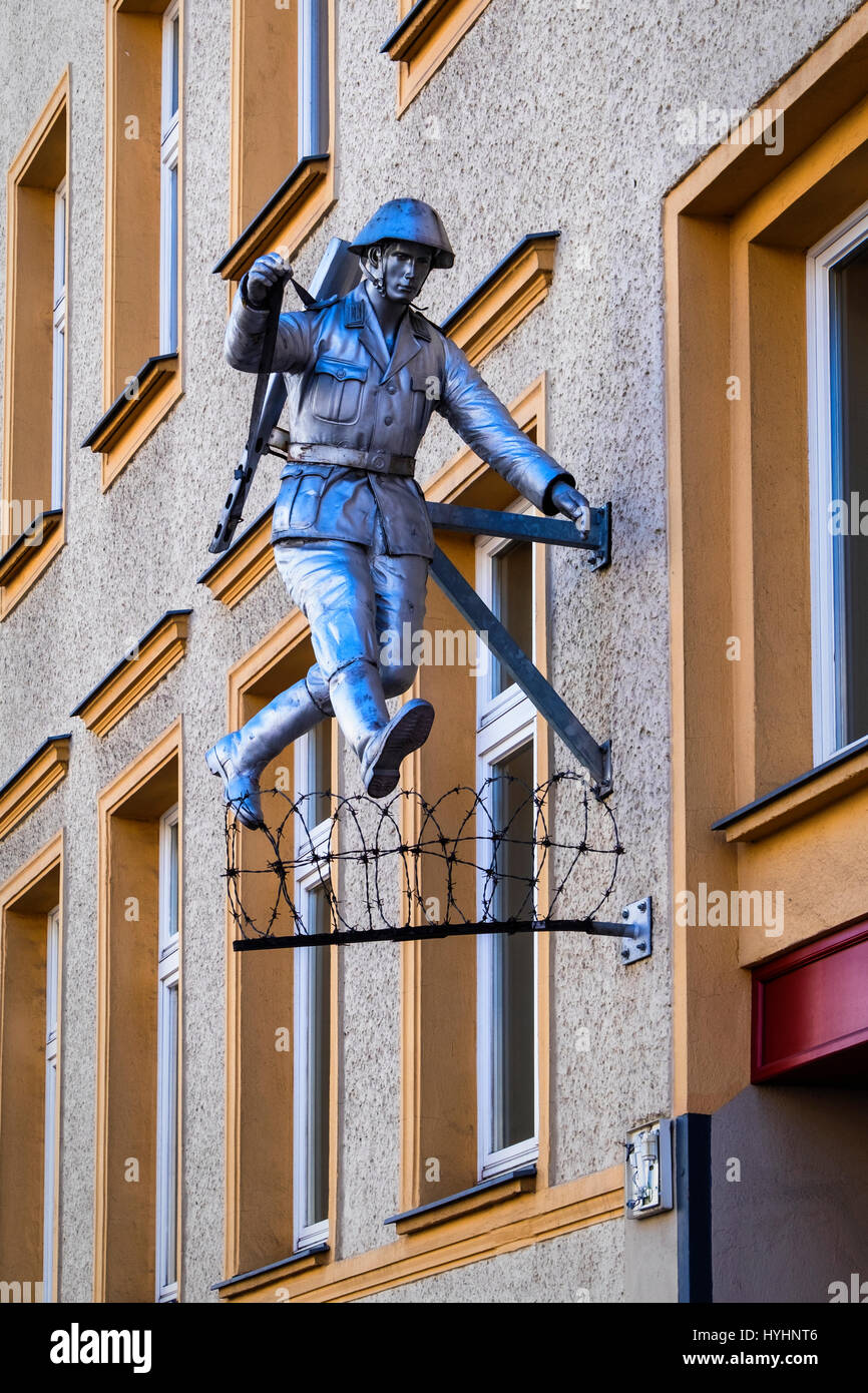 Berlin,Mitte.Wall jumper,Jumping soldier sculpture.East German Border guard, Conrad Schumann, jumps over barbed wire to escape from East Berlin during Stock Photo